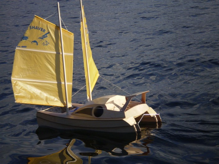 Beam reach with the lee sail sheeted to the forward bow, stern view.